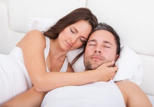 two people sleep happily in bed