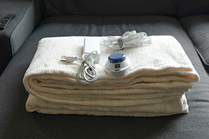 Folded electric blanket on dark couch